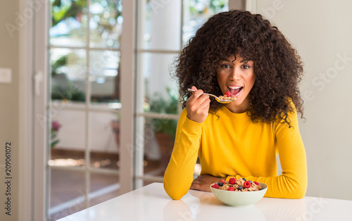Leinwanddruck Bild African american woman eating cereals, raspberries and blueberries with a confident expression on smart face thinking serious