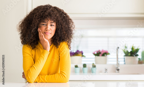 Leinwanddruck Bild African american woman wearing yellow sweater at kitchen touching mouth with hand with painful expression because of toothache or dental illness on teeth. Dentist concept.