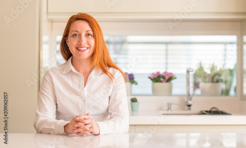 Leinwanddruck Bild Redhead woman at kitchen with a happy and cool smile on face. Lucky person.