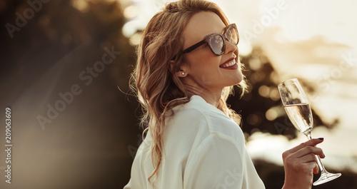 Uśmiechnięta kobieta pije wino w okularach przeciwsłonecznych