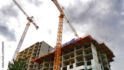 Fridge magnet Two construction cranes and building under construction. Construction site.