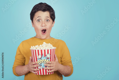happy boy with popcorn on blue background