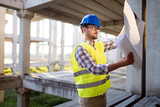 Architect holding rolled up blueprints at construction site - 209072075