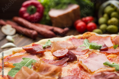 Delicious italian pizza with ham, bavarian sausages and prosciutto decorated by basil leaves on wooden background - 209072813