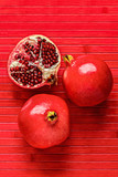 Whole and halved pomegranates, rich with sweet red seeds, on a red wooden background. They symbolize abundance and properity. - 209074042