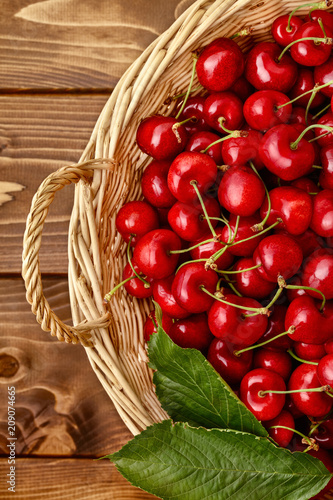 Aluminium Kersen Overhead view of freshly picked cherries in a wicker basket on a wooden background.