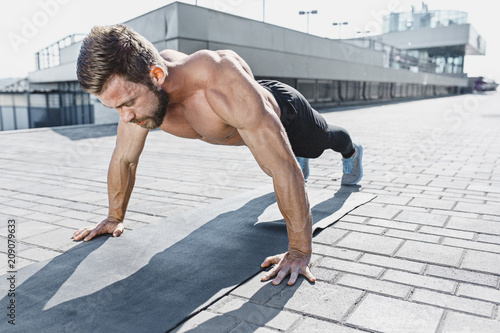 Poster Fit fitness man doing fitness exercises outdoors at city