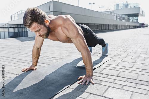 Dysponowany sprawność fizyczna mężczyzna robi sprawności fizycznych ćwiczy outdoors przy miastem