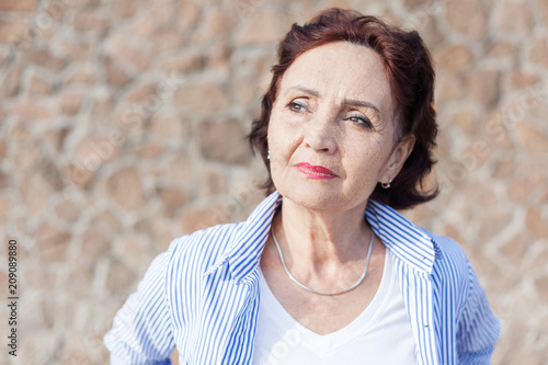 Portrait of a mature attractive stylish woman retired and outdoors on a summer sunny day