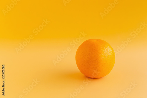 Fotobehang Sap Glass of orange juice freshly squeezed on an orange background