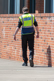 security guard in yellow hi vis with walkie taklie walking away from job on wooden decking by brick wall after being fired with head bowed - 209104215