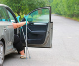 Disabled woman upgoing from a car. Transportation and travel for handicapped people. - 209104492