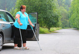 Disabled woman upgoing from a car. Transportation and travel for handicapped people. - 209104626