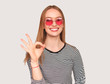 Trendy girl showing OK gesture on white