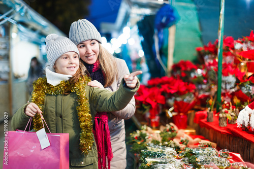 Leinwanddruck Bild Girl with woman choosing Christmas gifts for family