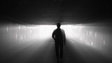 Silhouette of man walking in tunnel to the light. Concept of afterlife - 209108852