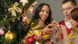 Leinwanddruck Bild - Loving parents helping their daughter to decorate Christmas tree, magic moments