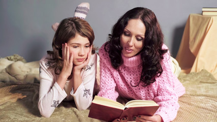 Mother reading aloud interesting storybook to her daughter, family values