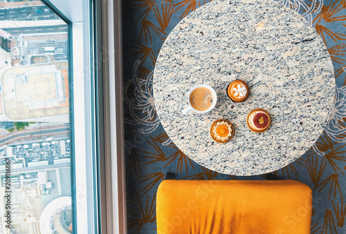 Wall mural Handcrafted gourmet fruit tarts and pastries with coffee high above the city