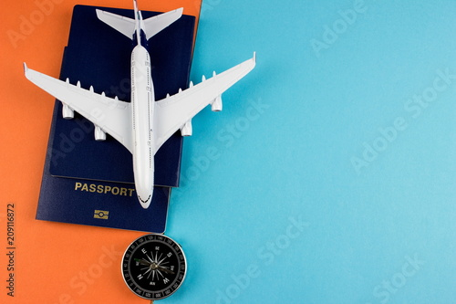 Travel concept with plane and passport on color paper background. Copy space for text and design