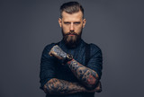 Handsome old-fashioned hipster in shirt and suspenders, pose with crossed arms. Isolated on a dark background. - 209118023