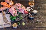 Preparation of rabbit meat for smoking. Raw rabbit legs, lime, onions, garlic, thyme and rosemary in rustic style, Sea salt, red, white pepper and coriander in clay pots on an old black rustic table.