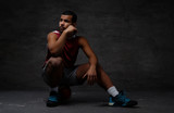 Pensive young African-American basketball player in sportswear sitting on a ball over dark background. - 209120030