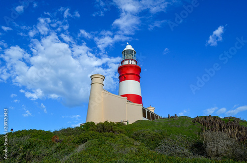Fotobehang Vuurtoren Beautiful lighthouse. Red and white lighthouse, view from bottom, blue sky with clouds on background