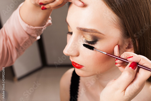 close up photo of make up artist carefully applying a mascara on lashes of a beautiful