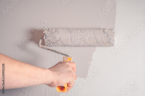 Hand painter paints the wall with a fur roller