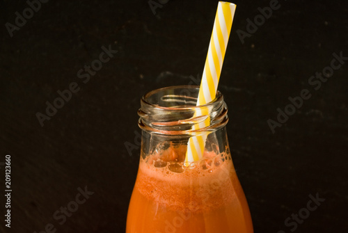 Fotobehang Sap carrot juice in a bottle with a straw close up