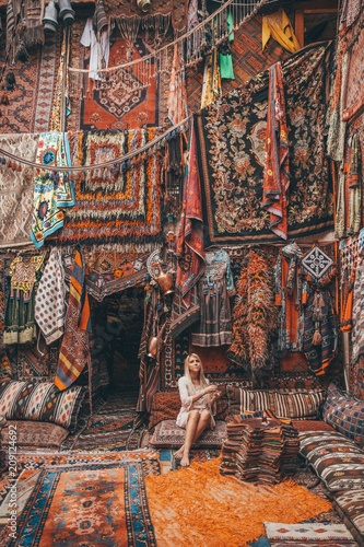 Poster Woman drinking a tea in a carpet store in Cappadocia