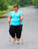 Overweight woman walking on forest trail. Slimming and active lifestyle theme.  - 209130023