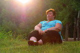 Overweight hiker woman relaxing and meditating in a deep forest. Active lifestyle and mental health theme.  - 209130204
