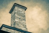 one big brick pipe of a flue against the background of the storm sky closeup vintage style - 209134275