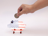 man putting coin into piggy bank with USA flag - 209137678