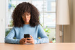 Leinwanddruck Bild - Beautiful african american woman using smartphone with a confident expression on smart face thinking serious