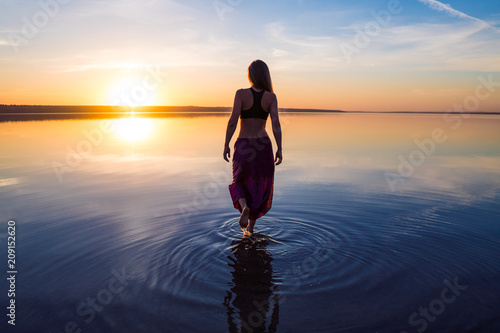 Silhouette woman on the beach at sunset . She stands in water. Morning natural stretch warm-up training