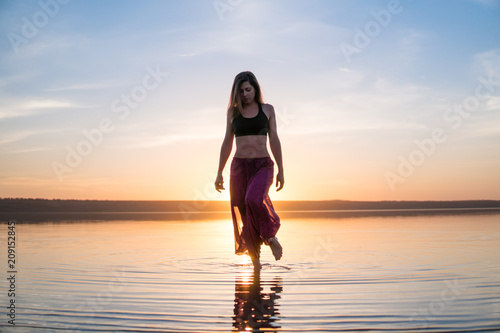 Wall mural Silhouette woman on the beach at sunset standing in water. Morning natural stretch warm-up training