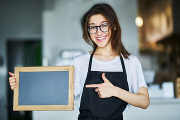 happy waitress holding blank chalkboard sign