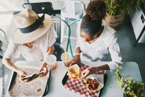 Foto Murales two friends eating healthy vegan food at restaurant together
