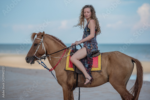 Happy smiling attractive blond wavy hair woman riding a horse on the Beach, relaxing time concept.