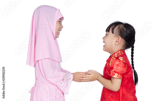7b230a291 Asian Chinese little sisters wearing cheongsam and traditional Malay costume  with greeting gesture
