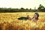 Cheerful girl in a field with wheat model aircraft - 209169099