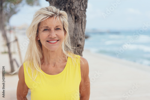 Leinwanddruck Bild Attractive tanned blond woman standing on a beach
