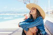 Happy vivacious young woman in a straw sunhat