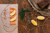 Sandwich with salmon, spices and lemon on a wooden table - 209175842