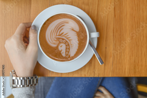 Foto Murales Girl in cafeteria with big cup of mocha and indian latte art on table for morning break