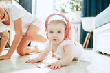 Cute young baby sitting on the floor at home playing with headphones - 209183468