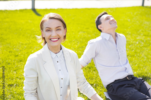 Short haircut. Smiling prosperous businesswoman with stylish short haircut smiling broadly feeling simply amazing